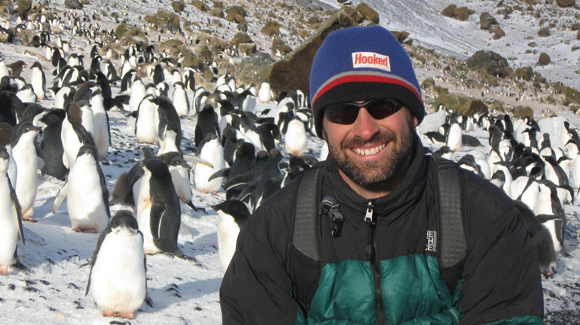 James Dziezynski and Adelie penguins in Antarctica